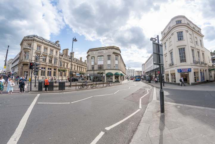 Cheltenham, United Kingdom - June 25, 2013: Pedestrians shopping on a busy city street in Cheltenham, England. Photograph shot with a Wide angle lens.